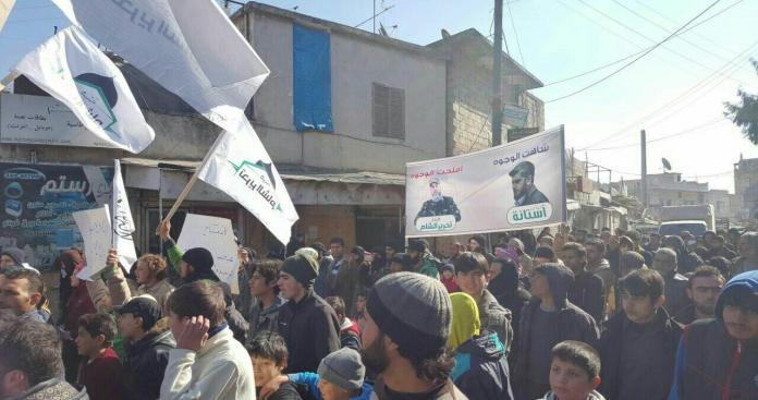 مؤيدين لهيئة تحرير الشام يرفعون لافتة في تظاهرة لهم تثير الجدل